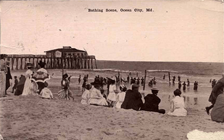 People enjoying a day on the beach by the oc fishing pier in 1900